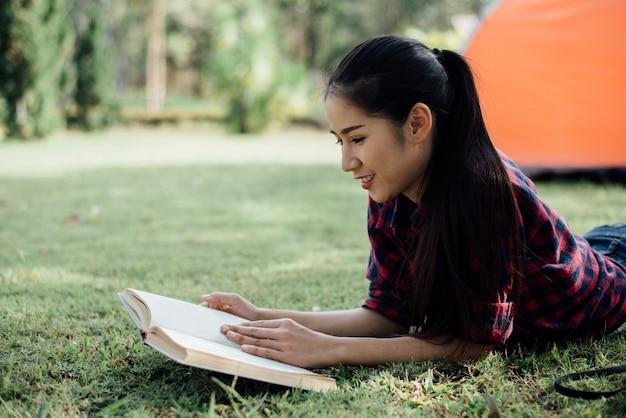 Muchacha hermosa en el bosque del otoño que lee un libro