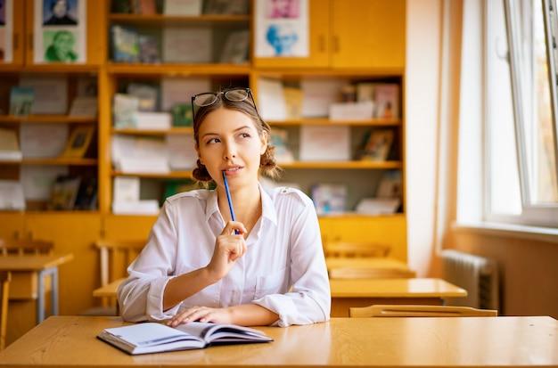Muchacha hermosa en una camisa blanca que se sienta en la tabla por la ventana en la sala de clase que lee un libro