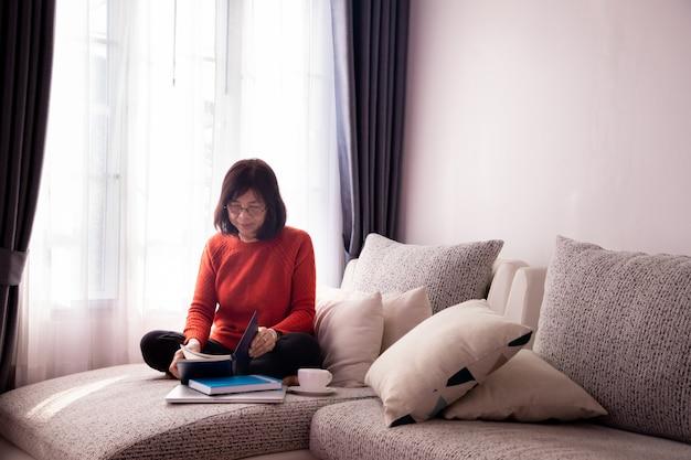 Muchacha hermosa en casa que se sienta en el sofá, leyendo un libro.
