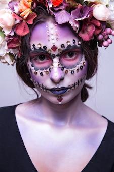 Muchacha hermosa de halloween con los rhinestones y la guirnalda de flores