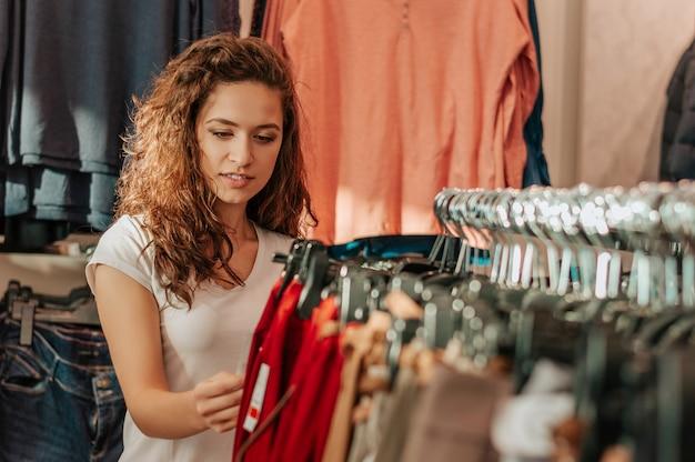 La muchacha hermosa elige la ropa en tienda.