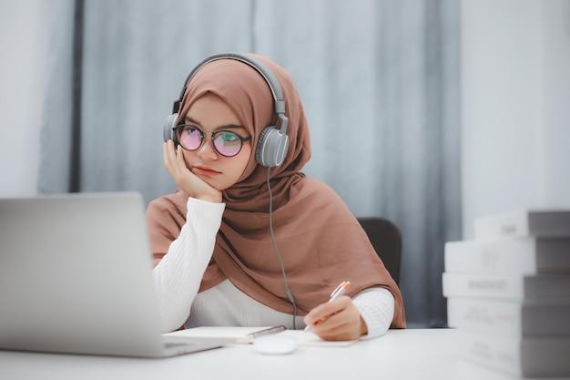 Muchacha hermosa del estudiante musulmán que usa una computadora portátil que aprende en línea en casa. educación a distancia en línea.