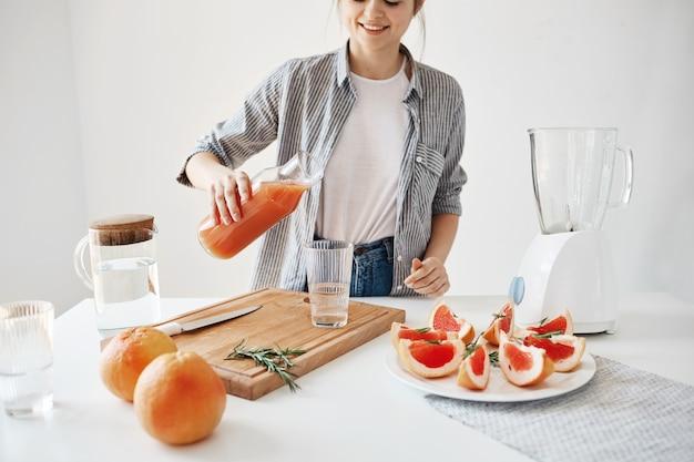 Muchacha hermosa feliz que vierte el smoothie de desintoxicación del pomelo en el vidrio que sonríe sobre la pared blanca. dieta saludable nutrición.