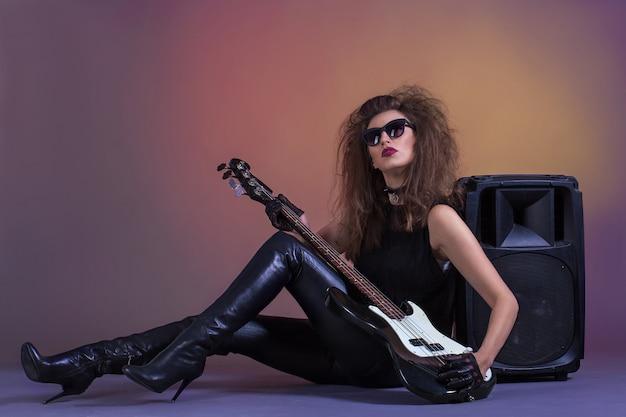 Muchacha hermosa con la guitarra baja en la ropa de cuero.