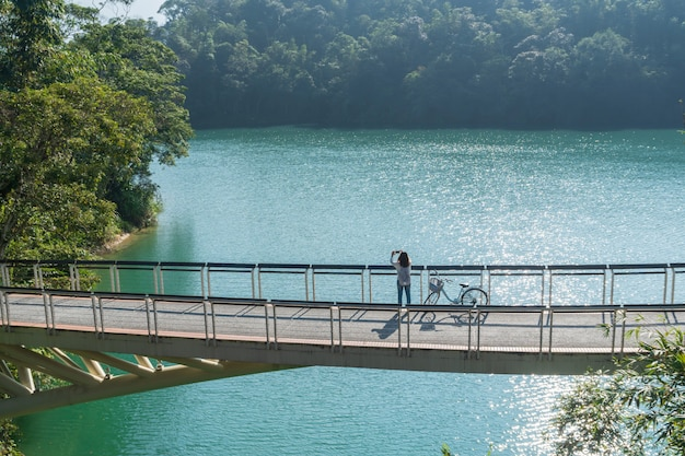 La muchacha hermosa joven se coloca cerca de una bicicleta mientras que toma una foto de la vista delante en el sendero de la bicicleta en el lago por la mañana. personas activas al aire libre