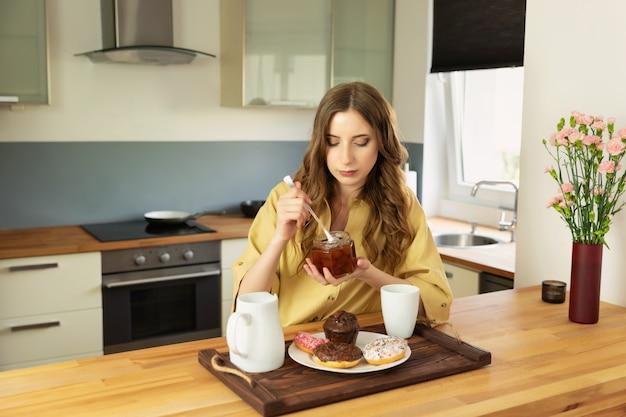 La muchacha hermosa joven está desayunando en casa en la cocina. ella toma su café de la mañana.
