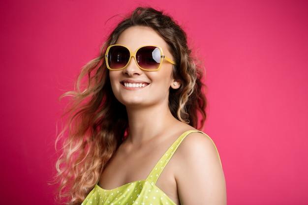 Muchacha hermosa joven en gafas de sol que sonríe sobre la pared rosada.