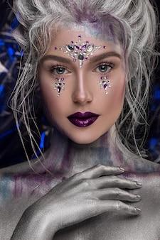 Muchacha hermosa joven en maquillaje creativo con el diamante artificial