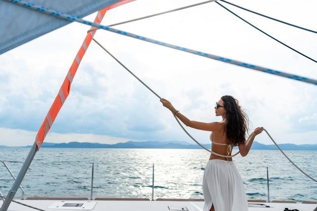 Muchacha hermosa joven con el pelo largo que se coloca en el arco del yate en la falda y el bikini blancos. vista trasera