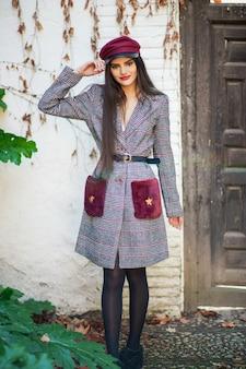 Muchacha hermosa joven con el pelo muy largo que lleva el abrigo de invierno y el casquillo en hojas de otoño