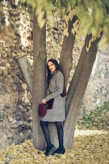 Muchacha hermosa joven con el pelo muy largo que lleva el abrigo de invierno y el casquillo en parque urbano por completo de las hojas de otoño