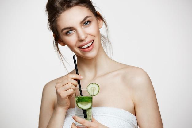 Muchacha hermosa joven con la piel limpia perfecta que sonríe mirando la cámara que sostiene el vidrio de agua con las rebanadas del pepino sobre el fondo blanco. nutrición saludable.