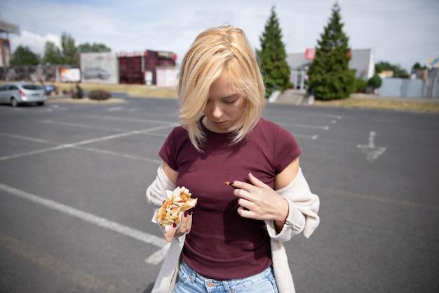 Muchacha hermosa joven que come el perrito caliente en el estacionamiento. ropa sucia por imprecisión.