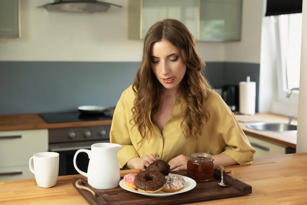 Muchacha hermosa joven que desayuna en casa en la cocina.