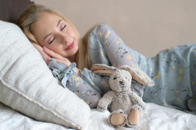 La muchacha hermosa joven que duerme en cama con el juguete del niño le gusta el niño.