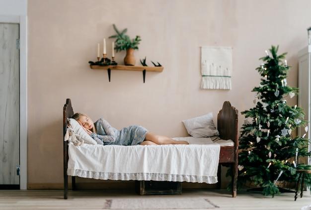 La muchacha hermosa joven que duerme en cama con el juguete tiene gusto del niño en sitio con el árbol de navidad.