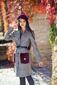 Muchacha hermosa joven que lleva el abrigo de invierno y el casquillo en fondo de las hojas de otoño.