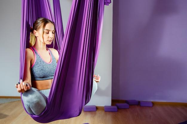 Muchacha hermosa joven que practica yoga aérea en gimnasio.