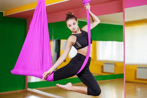Muchacha hermosa joven que practica yoga aérea en gimnasio
