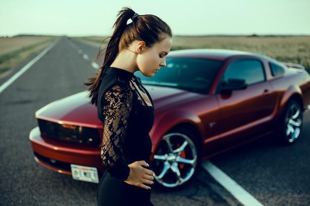Muchacha hermosa joven que presenta cerca del coche rojo costoso, coche potente