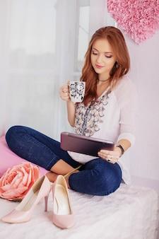 La muchacha hermosa joven se sienta con la tableta.
