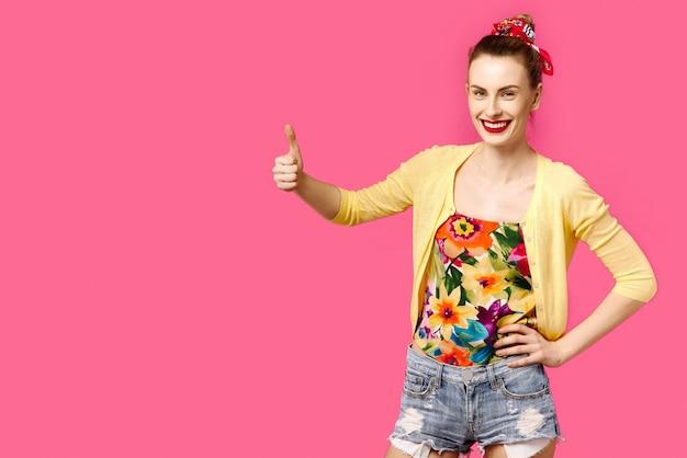 La muchacha hermosa joven en suéter amarillo en fondo rosado muestra el pulgar para arriba