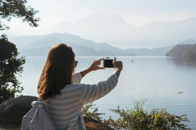 La muchacha hermosa joven toma una foto de la vista delante en el sendero de la bici en el lago por la mañana. personas activas al aire libre
