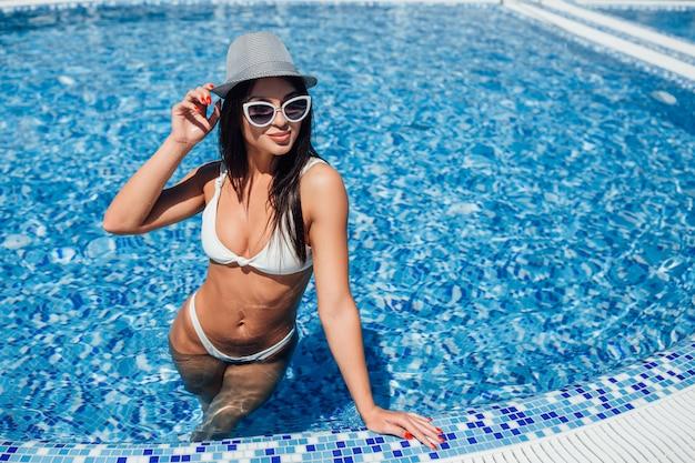 Muchacha hermosa joven en un traje de baño blanco, gafas de sol y sombrero con una figura hermosa