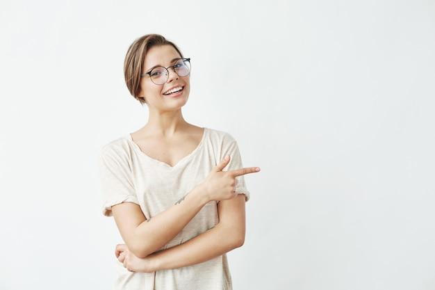 Muchacha hermosa joven en vidrios que sonríe señalando el dedo en lado.