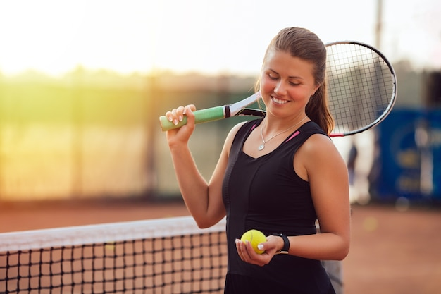 Muchacha hermosa juguetona que mira la pelota de tenis, colocándose en la corte con la raqueta.