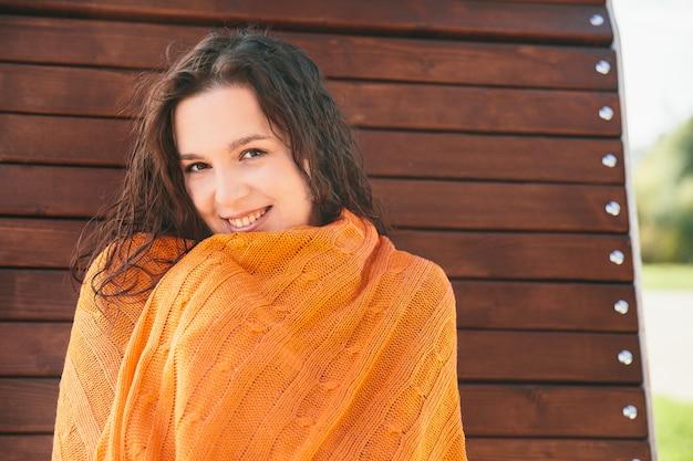 Muchacha hermosa en manta anaranjada en banco de madera en la corteza