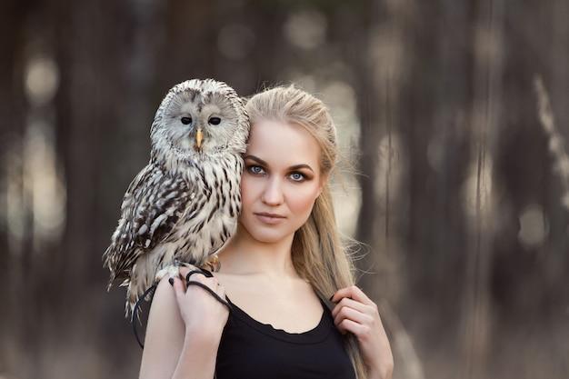 Muchacha hermosa con la naturaleza del pelo largo, sosteniendo el búho