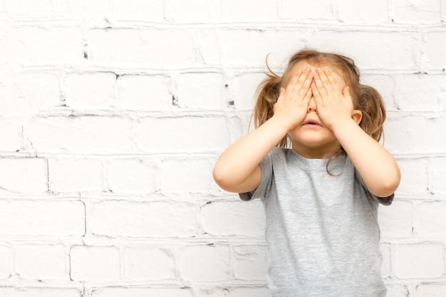 Muchacha hermosa del niño que cubre los ojos de sorpresa aislada sobre la pared de ladrillo blanco