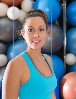 Muchacha hermosa de los ojos azules que sonríe en el retrato del gimnasio
