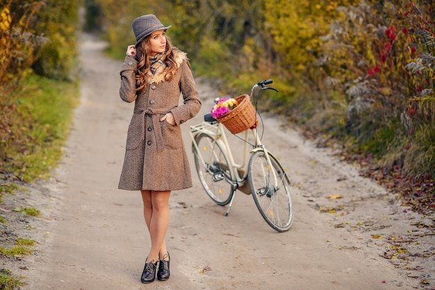 La muchacha hermosa en otoño marrón cubre y el sombrero que se coloca en el camino de tierra con la bicicleta de las señoras y los árboles del otoño en el fondo.
