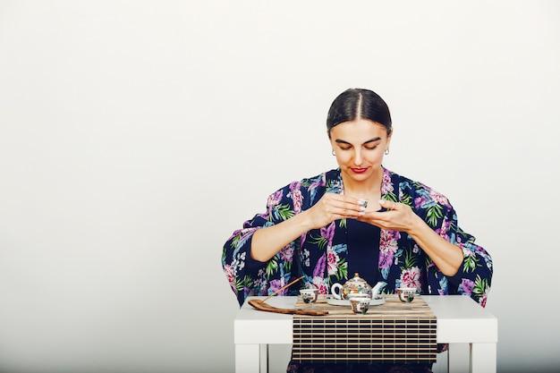 Muchacha hermosa que bebe un té en un estudio