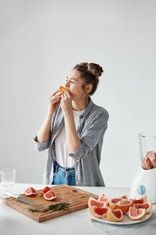 Muchacha hermosa que come el pedazo del pomelo sobre la pared blanca. nutrición saludable y saludable. copia espacio