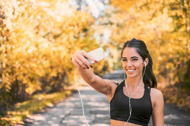 Muchacha hermosa que sonríe y que toma el selfie mientras que corre en parque.