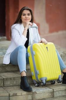 Muchacha hermosa que sostiene una maleta amarilla grande.