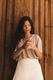 Muchacha hermosa que sostiene la taza de café disponible que se opone a puerta de madera