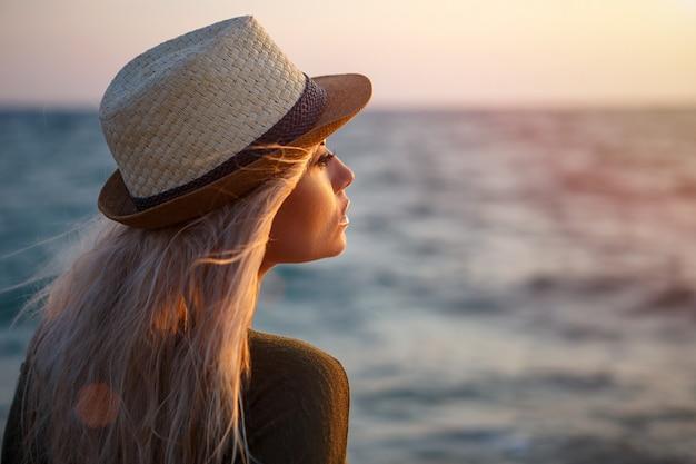 Muchacha hermosa en sombrero por el mar en la puesta del sol.