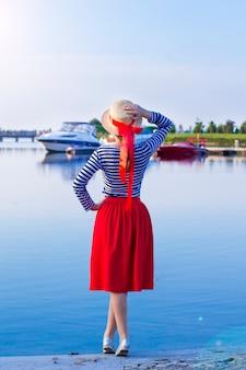 La muchacha hermosa en un sombrero de paja en el embarcadero cerca del mar navega y los barcos.