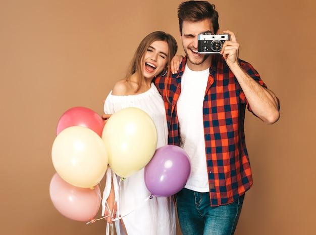 Muchacha hermosa sonriente y su novio hermoso que sostiene el manojo de globos coloridos. feliz pareja tomando fotos de sí mismos en la cámara retro. feliz cumpleaños