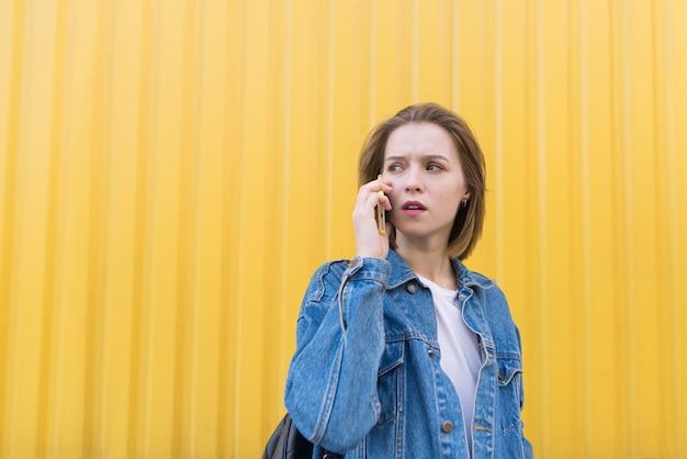 Muchacha hermosa sorprendida que habla en el teléfono en fondo de la pared amarilla y que mira de lado.