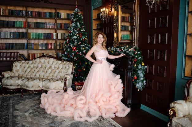 Muchacha hermosa en vestido enorme cerca del árbol de navidad.