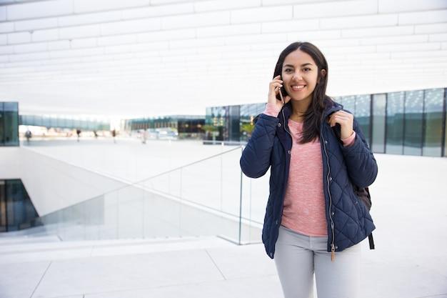 Muchacha india alegre del estudiante que habla en el teléfono móvil