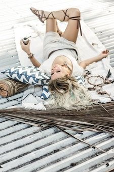 Muchacha india hermosa del hippie con el pelo rubio largo en el té de consumición del compañero del tejado.