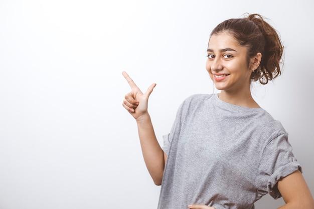 La muchacha india sonriente muestra los dedos en el espacio de la copia