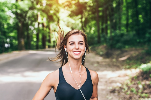 Muchacha joven de la aptitud que corre y que escucha música en el parque