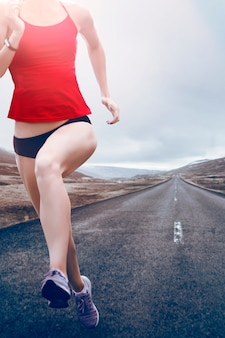 Muchacha joven de la aptitud que lleva top rojo, pantalones cortos negros, zapatillas de deporte que corren en el camino